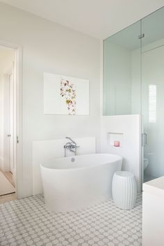 The pool's graphic design inspired the flooring in the master bath. The gray-and-white tiles here are also from Mosaic House, but feature a more contemporary pattern. The soaking tub is by Victoria & Albert.