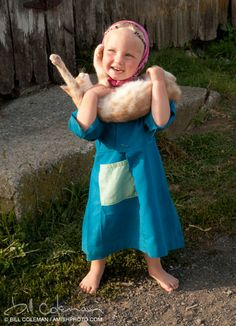 Amish girl with a little cat.  She's so happy. Look at that smile!