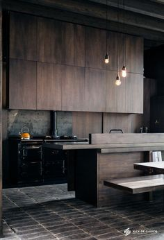 moody industrial style kitchen with timber cabinets and a black freestanding cooker