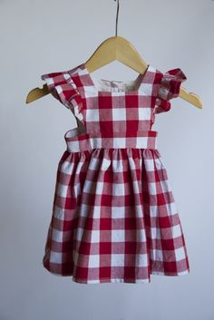 Red gingham print pinafore. 100% Cotton. 3 buttons down the side.*WILL SHIP ON THE 15-16th of MAY**Check out the size chart, for the correct size.*Care: Machine wash on delicate cycle. Tumble dry on low or lay out to dry. Press with warm iron if desired.