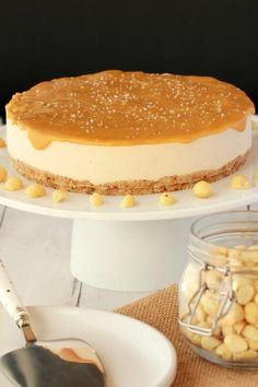 Vegan Cheesecake with salted caramel topping on a white cake stand. A bowl of macadamia nuts and a cake lifter and white serving dish in the foreground.