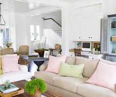 Give an au naturel look a garden spin with blooms of pink. This welcoming family room -- with plenty of wood tones, neutral linen fabrics, and wicker accents -- gets a flowery finish with the addition of pale pink throw pillows.