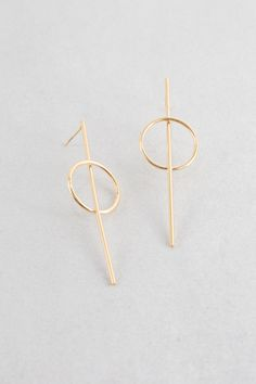Minimal gold circle and bar stud earrings.