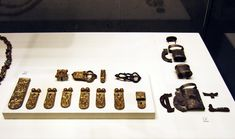 Man's grave goods from Zamárdi, Hungary. Avar. Man's grave, late 6th to early 7th century. At his foot end the burial of a horse. 1. Belt buckle, main strap end and seven side strap ends ornamted with incised dental decor. 2. Rolled silver mounts of the cross guard of a sword and the matching sheath.