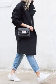 White trainers with an oversized black coat for an easy scandi style.
