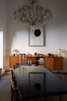 Carolina Castiglioni Nella zona pranzo, tavolo da riunione laccato di nero e un lampadario a gocce di cristallo. Sull'armadio, la collezione di sedie in miniatura Vitra di Carolina