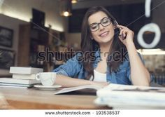 Smiling young woman talking on phone in cafe