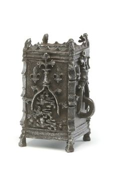Title:  Metal almsbox: 15th century    Description:  Rectangular metal almsbox, standing on small feet. It is decorated with fleur-de-lis and heraldic lions. This iron box has a slot in the top to take coins and a ring on one side so that it could be chained securely in place to prevent theft. It is skilfully made of wrought iron. It was a Christian duty to give to the poor, and there were alms boxes in churches and many other places.