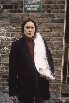 Sarah Lucas 'Got a Salmon On #3', 1997 © Sarah Lucas  In Got a Salmon On #3 1997 (P78451) Lucas stands outside a public toilet, a huge salmon resting from her shoulder to below her waist, a pun on the idea of a female erection.