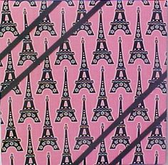 """Fabric Cork Bulletin Boards.   Eiffel Towers on Pink background with black diagonal  message ribbons, 12"""" x 12"""""""" $24.20, or, YOUR choice of over 1000 fabrics, or YOUR fabric; four standard sizes or custom size; with or without message ribbons; and lots more at  www.PushPinsAndFabricCorkBoards.com,  Category: FABRIC CORK BULLETIN BOARDS, Subcategory: TRAVEL. Also matching DECORATIVE PUSH PINS. #fabriccorkbulletinboards #decorativepushpins #fleur de lis #France #French #EffielTower# Paris"""