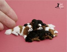 A pile of dollhouse miniature sleeping English Toy Spaniels -- All 5 dogs were freehand sculpted independently and after applying the soft furry coats, were reassembled into a single display piece.
