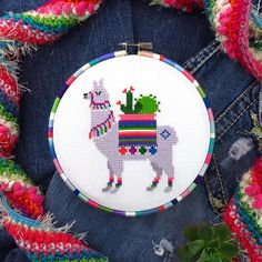 A colorful Llama cross stitch pattern that will brighten any home! Featuring a cute cross stitch llama with a decorative harness, blanket and socks, as well as a small cactus garden being transported on its back, this llama needlework really stands out with rainbow Mexican colors. A
