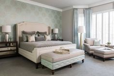 Beautifully designed master bedroom with accent wall, a light green floral patterned as wallpaper that cover the wall behind the master bed, that has a large headboard.
