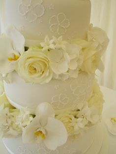 Four tier iced wedding cake with lace piping and fresh flowers