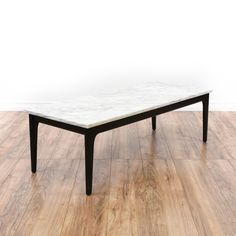 This mid century modern coffee table is featured in a solid wood with a sleek black paint finish. This coffee table has a large white marble table top with gray veining and tapered legs. Stylish table perfect for holding drinks! #midcenturymodern #tables #coffeetable #sandiegovintage #vintagefurniture