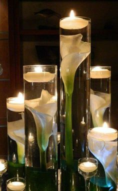 Flowers cut at various lengths submerged in water with floating candles