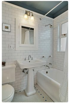 Add a pop of color to a white bathroom by painting the ceiling! Loving the dark ceiling against the white subway tile in this bathroom.