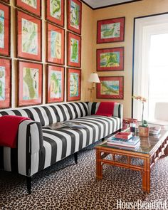 An upstairs TV room is dominated by a long sofa covered in Perennials' Bigger Stripe. Walls are clad in Phillip Jeffries's Driftwood grass cloth and trimmed with Samuel & Sons' French grosgrain ribbon. Floor lamp, Visual Comfort.