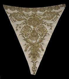 Title: Bodice Inset Embroidered with a Stylized Plant Motif Place of creation: Western Europe (France ?) Date: First half of 18th century Material: silk (ground), gold thread, wire, sequins, twist and metal-thread lace Technique: embroidery in raised laid and couched stitches technique Inventory Number: Т-2236