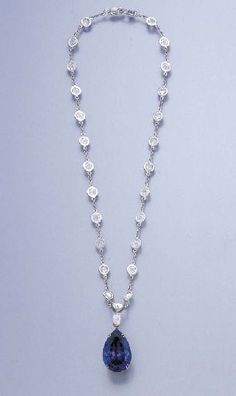A TANZANITE AND DIAMOND PENDANT NECKLACE  The pear-shaped tanzanite, weighing approximately 20.12 carats, suspended by pear and triangular-shaped rose-cut diamond links, from the fine-link neckchain with diamond collet spacers, 37.0 cm.