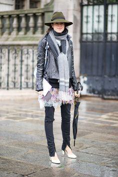 Leandra Medine in biker jacket, sheer flower patterned tunic, black leggings, white heels, olive fedora hat. Paris Fashion Week, Street style.