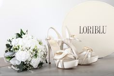 LORIBLU. Ivory satin sandal with stiletto heel and platform. The calla lily flower at the toe makes it a refined and romantic slyle for ceremony. Available at Loriblu boutiques and http://www.loriblu.com/en/sposa/sposa-calzature/sandalo-gioiello-4ex02155xc2c01469po.html?___from_store=en