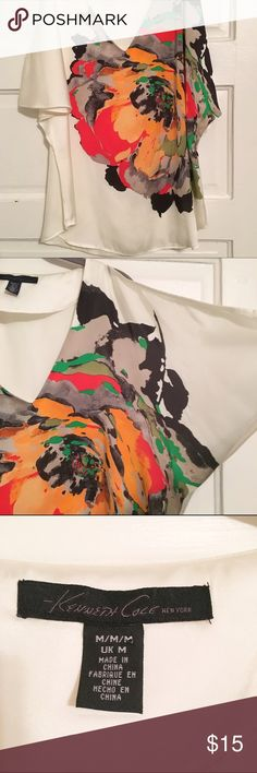 Kenneth Cole Vibrant Flower Cold Shoulder Top Make a statement in this cold shoulder blouse by Kenneth Cole. Gorgeous flower in red-orange, orange, olive, gray, black, and bright green on an ivory base. Great condition, just has a couple of snags as seen in last photo. Don't see them unless you're searching! I would personally pair with a black pencil skirt, bit would work great with any black or ivory bottom, or skinny jeans with heels in one of the vibrant colors. Kenneth Cole Tops Blouses