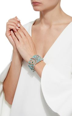 Delicatedly embellished with white diamonds, this scintillating bangle features glistening paraiba tourmalines throughout an intricate curvilinear design.