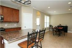 Island kitchen with granite counters, open to the dining area. #ForSale #Kitchen #Dining