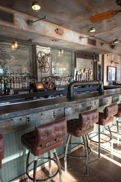 the entire of this bar area has been designed with a distressed look. the dark leather upholstered seats complement the pale chalky blue bar area well. wood panelling on the walls and floor tie the space together well.