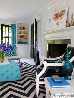 Black, white, and turquoise make a graphic splash in fashion designer Liz Lange's house in Westchester County, New York. Decorator Jonathan Adler designed most of the furnishings and accessories, including the living room's generous ottoman upholstered in Hinson's Montauk Texture in Aegean, the Herringbone rug, and the black patent leather Regent armchair. Knoll Barcelona chairs from Design Within Reach. - HouseBeautiful.com
