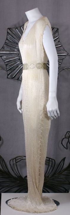 Mariano Fortuny Off White Silk Delphos Gown This dress is made of finely pleated off white colored silk with silk cording along side seams and clear striped glass beads threaded through the cording.