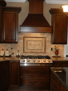 Focal point of this maple dark kitchen is this wood hood. Ventillation is a must in your kitchen design
