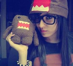 Brunette wearing nerdy glasses holding stuffed animal