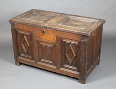 """Lot 904, A 17th/18th Century oak coffer of panelled construction with hinged lid, the interior fitted a candle box with long iron hinges, 24""""h x 31""""w x 19 1/2""""d Est £200-300"""