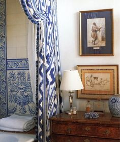 Blue and white Ikat drapes, blue & white tile & border with chest & lamp in the bath.