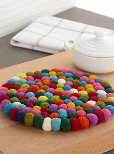 Une pièce d'art artisanal pour la table avec cet assemblage de petits pompons de laine au flair rétro chic très tendance en déco.    Feutre de laine souple et luxueux   Fait à la main au Népal   20 cm rond