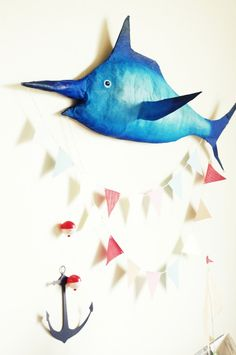 a big blue paper mache marlin  and decorative garlands using craft paper and kitchen twine.