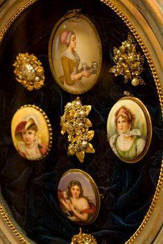 Painted porcelain and rhinestone brooches on velvet, framed.