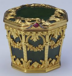 Fabergé octagonal box of nephrite, mounted in gold with a hinged lid with border of pierced Rococo scrolls and a cabochon ruby and rose diamond thumb-piece, tapering sides to base mounted with spiral columns supporting foliate arches, hung with swags. Mark of Erik Kollin. Acquired by Queen Mary by 1913.
