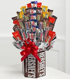 """The Sweets in Bloom® Chocolate Lover's Dream Bouquet is the perfect way to share in their special occasion or celebration, indulging their sweet-tooth and giving them what they most crave. 6 Full size Milk Chocolate Hershey® Bars create a tempting """"vase"""" while 15 """"blooms"""" of snack-size bars in assorted varieties make a most mouth-watering bouquet. A unique gift your chocolate lover is sure to rave about!"""