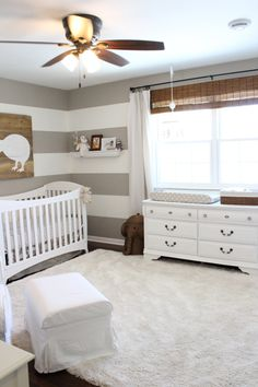 Gender neutral nursery with striped walls and a cozy rug