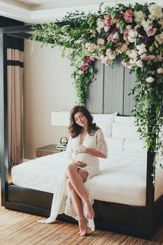 Expecting mother sits elegantly on her bed with running green and florals across the bed frame // Earlier this year we featured Miss Universe Malaysia Carey Ng's helipad wedding, and today we're delighted to share our styled maternity shoot photos with the bride-turned-mother-to-be. Carey is in the pink of health and glows in these images captured by Munkeat and styled by Agnes of Prep at The Majestic Hotel Kuala Lumpur.