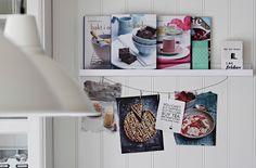 Duas prateleiras para molduras com livros de receitas e receitas recortadas em exposição