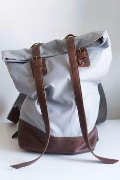 Duży plecak z szarej tkaniny ortalionowej ze skórzanymi dodatkami. Góra plecaka o regulowanej wysokości.