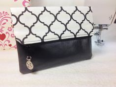 By Phenomenal Women Shop, The modern white and black quatrefoil made from 100% cotton, sits atop the lack vegan leather banned bottom. The interior is fully lined in Kona black.  This foldover clutch has a zippered closing for extra security and style, that is adorned with a Tree of Life charm for the zipper pull.