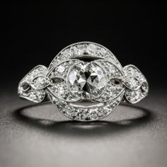 Dating from the second decade of the last century, this ravishing, radiant and genuinely original and unique vintage jewel can be construed as either late-Edwardian or early-Art Deco in style, or better yet, an artful blending of each. Centering on a bright white and sparkling European-cut diamond, weighing just over a half-carat, the curvaceous design is composed of glittering diamond-set ribbons accentuated with delicate milgrain edges. A dazzling delight. Currently ring size 6 1/2.