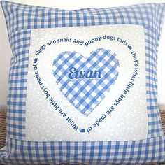 Personalised Baby Boy Cushion. Blue gingham heart & child's name in the centre. Message around heart reads: What are little boys made of, slugs and snails and puppy dogs tails, that's what little boys are made of.