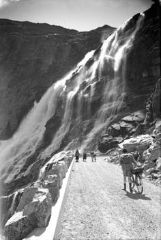 Dappere fietsers en voetgangers in vroeger tijden op de Trollstigen. Op de achtergrond de waterval Stigfossen, Noorwegen.