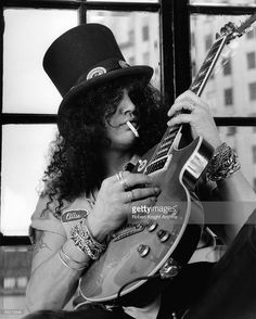 GUNS N' ROSES and SLASH; Slash, posed, studio, smoking cigarette, holding Gibson Les Paul guitar